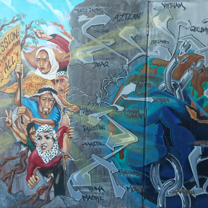 A section of a mural painted by Homies Organizing the Mission to Empower Youth (HOMEY) in the San Francisco Mission District depicting Palestinian people of various ages breaking through a wall. The wall has aerosol art images on it and lists the names of many nations and peoples including Ohlone, Aztlan, Iraq, Palestine, Haiti, Roma, Maori, East Timor, Afrika, Afrikan Diaspora, Philippines, Moro, Chamoru, and Ireland. (Photo: M. Horton, 2016)